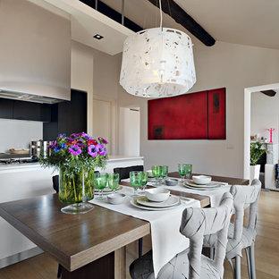Idée de décoration pour une salle à manger ouverte sur la cuisine design avec un mur blanc et un sol en bois clair.
