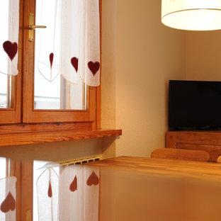 Modelo de comedor rural, pequeño, abierto, con paredes beige, suelo de madera en tonos medios, chimenea de esquina, marco de chimenea de madera y suelo rosa