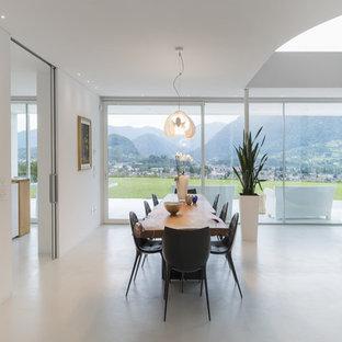 Ejemplo de comedor actual, abierto, con paredes blancas, chimeneas suspendidas, marco de chimenea de metal y suelo blanco