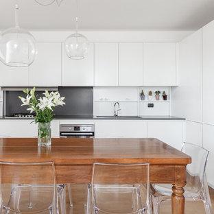 Idee per una sala da pranzo aperta verso la cucina contemporanea con pareti bianche, pavimento in legno massello medio e pavimento marrone