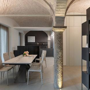 Immagine di una sala da pranzo mediterranea con pareti bianche e pavimento grigio