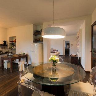 Cette image montre une grand salle à manger ouverte sur la cuisine style shabby chic avec un mur blanc et un sol en bois brun.
