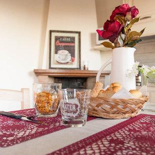 Imagen de comedor rústico, pequeño, abierto, con paredes blancas, suelo de baldosas de terracota, chimenea de esquina, marco de chimenea de ladrillo y suelo rosa
