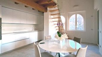 Cucina bianca open space con travi a vista e soppalco