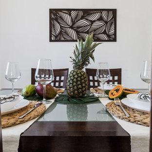 Immagine di un'ampia sala da pranzo aperta verso il soggiorno tropicale con pareti bianche e pavimento beige