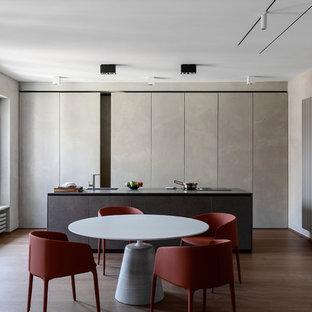 Idee per una sala da pranzo aperta verso la cucina contemporanea con pareti grigie, pavimento in legno massello medio e pavimento marrone