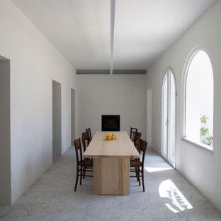Immagine di una sala da pranzo mediterranea chiusa e di medie dimensioni con pareti bianche, camino classico, cornice del camino in intonaco e pavimento grigio