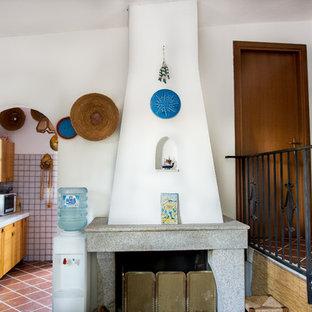 Immagine di una sala da pranzo costiera con pareti bianche, pavimento in gres porcellanato, camino classico, cornice del camino in pietra e pavimento marrone
