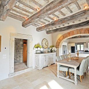 Esempio di un'ampia sala da pranzo aperta verso il soggiorno country con pavimento in pietra calcarea, pavimento beige e pareti bianche