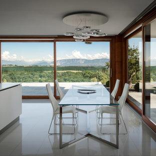 Foto di una sala da pranzo aperta verso la cucina minimalista con nessun camino e pavimento grigio