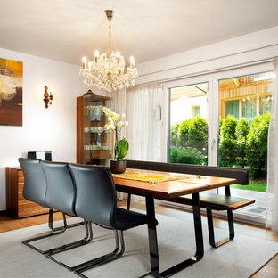 Immagine di una sala da pranzo mediterranea chiusa con pareti bianche, pavimento in legno massello medio e pavimento marrone