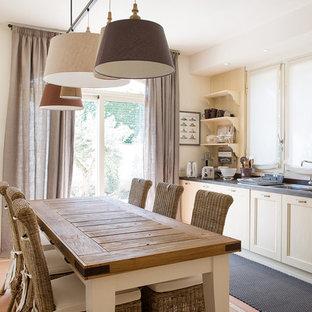 Esempio di una sala da pranzo aperta verso la cucina country di medie dimensioni con pareti bianche, pavimento in terracotta e pavimento arancione