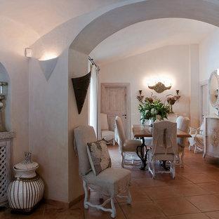 Immagine di una sala da pranzo aperta verso il soggiorno mediterranea di medie dimensioni con pareti bianche, pavimento in terracotta e pavimento rosa