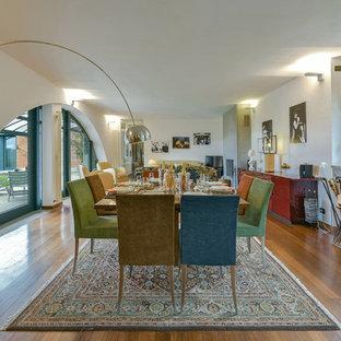 Ispirazione per una grande sala da pranzo aperta verso il soggiorno design con pareti bianche, pavimento in legno massello medio, camino classico, cornice del camino in pietra e pavimento marrone