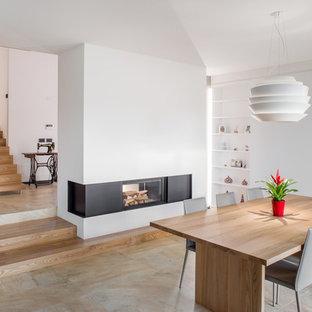 Idee per una sala da pranzo aperta verso il soggiorno contemporanea con pareti bianche, camino bifacciale e pavimento beige