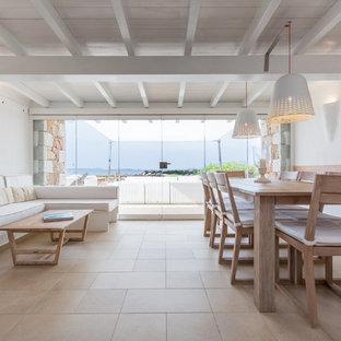 Foto di una sala da pranzo aperta verso il soggiorno costiera con pareti bianche e pavimento beige