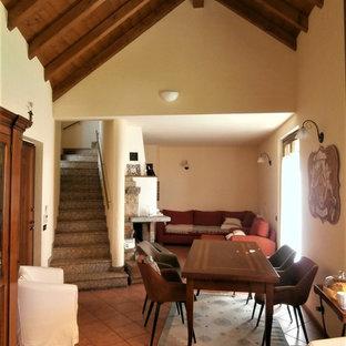 Immagine di una sala da pranzo chic con pareti bianche, pavimento in gres porcellanato, camino classico, cornice del camino in pietra e pavimento rosso