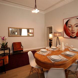 Eklektisk inredning av en mellanstor separat matplats, med beige väggar, en öppen hörnspis, beiget golv, ljust trägolv och en spiselkrans i gips