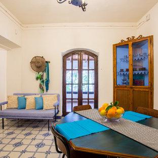Foto di una sala da pranzo aperta verso il soggiorno stile marino di medie dimensioni con pareti bianche, pavimento con piastrelle in ceramica, camino classico, cornice del camino in intonaco e pavimento multicolore