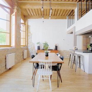 Cette photo montre une salle à manger ouverte sur le salon industrielle avec un mur beige, un sol en bois clair, aucune cheminée et un sol beige.