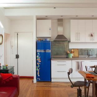 Réalisation d'une salle à manger ouverte sur la cuisine design de taille moyenne avec un mur blanc et un sol en bois brun.