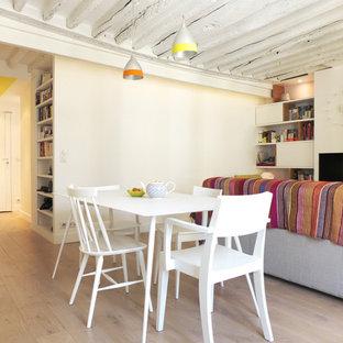 Cette image montre une salle à manger ouverte sur le salon design de taille moyenne avec un mur blanc, un sol en bois clair et cheminée suspendue.