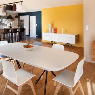Réalisation d'une grande salle à manger ouverte sur le salon design avec un sol en bois clair, un mur jaune et aucune cheminée.