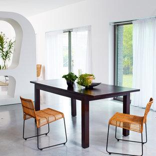 Réalisation d'une salle à manger ouverte sur le salon design de taille moyenne avec un mur blanc et béton au sol.