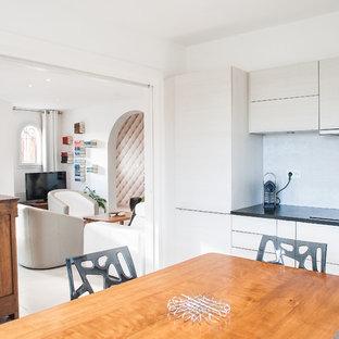 Aménagement d'une salle à manger ouverte sur la cuisine contemporaine de taille moyenne avec un mur blanc.