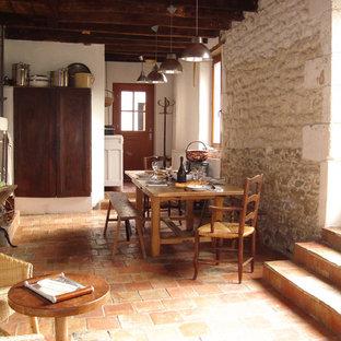 Cette image montre une grande salle à manger ouverte sur le salon rustique avec un mur beige, un sol en carreau de terre cuite et un sol orange.