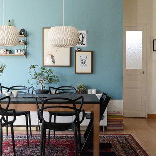 Inspiration pour une salle à manger ouverte sur le salon design de taille moyenne avec un mur bleu, un sol en bois clair et aucune cheminée.