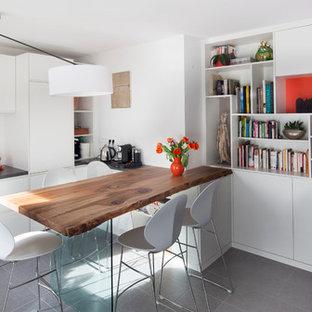 Idées déco pour une salle à manger ouverte sur le salon contemporaine de taille moyenne avec un mur blanc et un sol en ardoise.