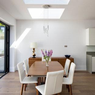 Aménagement d'une grand salle à manger ouverte sur le salon contemporaine avec un mur blanc, aucune cheminée, un sol marron et un sol en bois foncé.