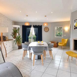 リヨンの大きいミッドセンチュリースタイルのおしゃれなダイニング (グレーの壁、セラミックタイルの床、標準型暖炉、レンガの暖炉まわり、白い床) の写真