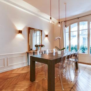 Exemple d'une grande salle à manger chic fermée avec un mur blanc, un sol en bois clair et aucune cheminée.