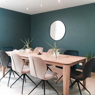 Aménagement d'une salle à manger contemporaine avec un mur vert, aucune cheminée et un sol beige.