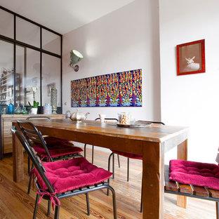 Inspiration pour une salle à manger bohème fermée avec un sol en bois brun et un mur beige.