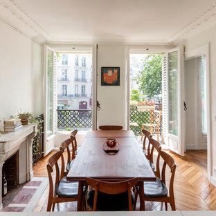 Ispirazione per una sala da pranzo mediterranea di medie dimensioni con pareti bianche, pavimento in legno massello medio e camino classico