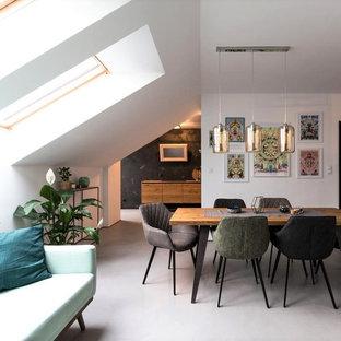 Aménagement d'une salle à manger ouverte sur le salon contemporaine avec un mur blanc et un sol gris.