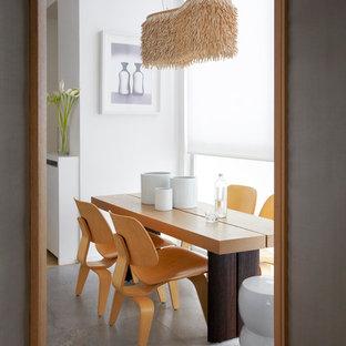 Inspiration pour une salle à manger nordique fermée et de taille moyenne avec un mur blanc, béton au sol et aucune cheminée.