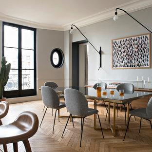 Idées déco pour une salle à manger ouverte sur la cuisine contemporaine avec un mur gris, un sol en bois brun et un sol marron.