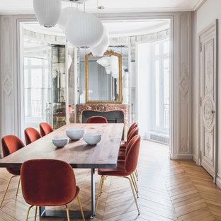 Cette photo montre une salle à manger tendance avec un mur blanc, un sol en bois brun, une cheminée standard, un manteau de cheminée en brique et un sol marron.