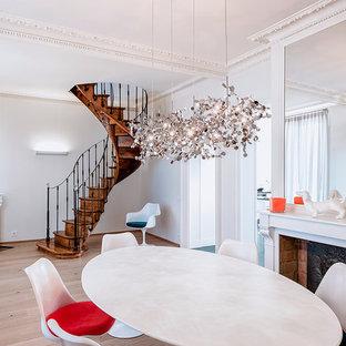 Exemple d'une salle à manger éclectique fermée et de taille moyenne avec un mur blanc, un sol en bois clair et une cheminée standard.