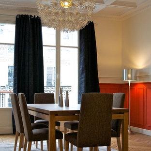 Cette image montre une salle à manger design fermée et de taille moyenne avec un mur rouge et un sol en bois brun.