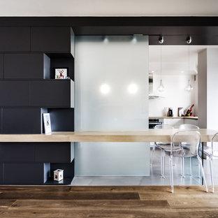 Idée de décoration pour une salle à manger ouverte sur la cuisine design avec un mur blanc et un sol en bois brun.