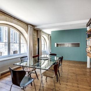 Cette image montre une grande salle à manger urbaine fermée avec un mur bleu et un sol en bois brun.