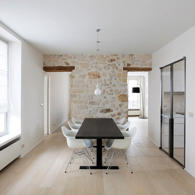 Example of a large trendy light wood floor enclosed dining room design in Paris with white walls and no fireplace