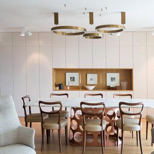 Aménagement d'une grand salle à manger ouverte sur le salon contemporaine avec un mur blanc, un sol en bois clair et un sol beige.