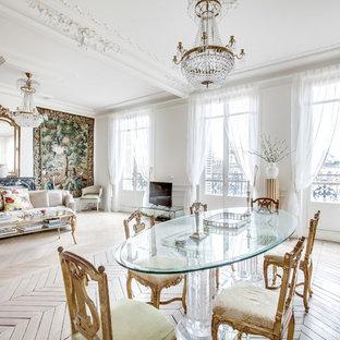 Réalisation d'une salle à manger ouverte sur le salon tradition avec un mur blanc, un sol en bois clair, une cheminée standard, un manteau de cheminée en pierre et un sol beige.