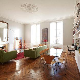 Пример оригинального дизайна: гостиная-столовая в стиле фьюжн с белыми стенами и паркетным полом среднего тона